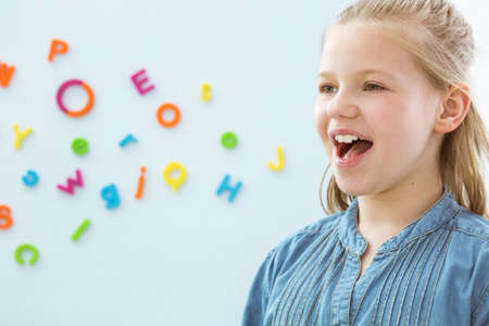 Foto de Copy space with little girl opening mouth in speech therapy office - Imagen libre de derechos