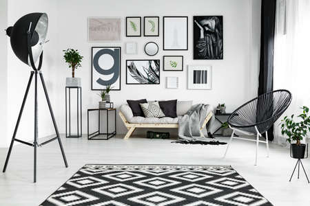 Photo for Stylish white living room with black accessories and plants - Royalty Free Image