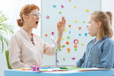 Foto per Special education teacher working with little girl during speech therapy - Immagine Royalty Free