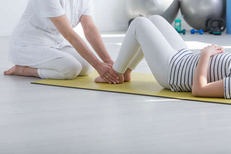Photo for Physiotherapist exercising with patient with faulty posture on foam mat - Royalty Free Image