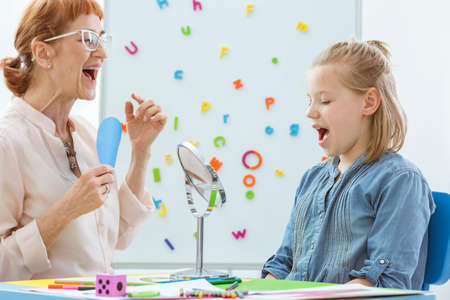 Foto per School counselor during speech and language rehabilitation with small girl - Immagine Royalty Free
