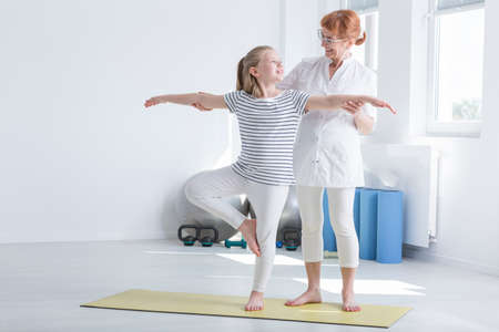 Photo for Child exercising with positive female physiotherapist in bright gymnastics room - Royalty Free Image