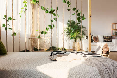 Photo pour Inspiring rope and ivy decorative room divider next to elegant bed in original apartment - image libre de droit