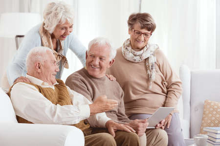 Photo pour Elderly couples using technology while enjoying each others company - image libre de droit