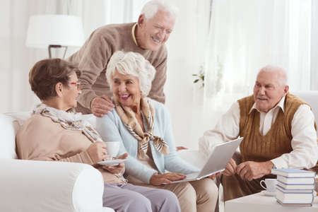 Photo pour Friendly conversation of elderly neighbors drinking tee, and using laptop - image libre de droit