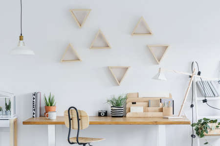 Photo for White scandi interior with wooden desk, triangle shelves and plants - Royalty Free Image