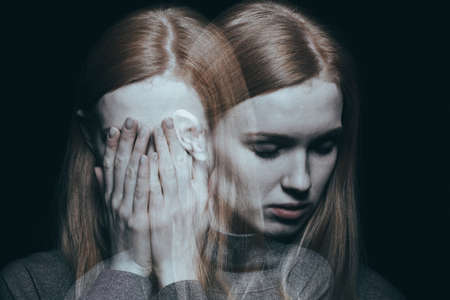Foto de Young girl covering her face with her hands after reaching a peak of her depression - Imagen libre de derechos