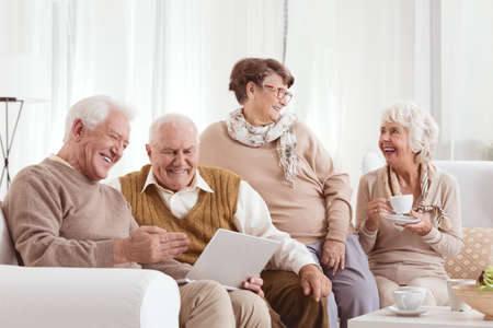 Photo pour Elderly friends relaxing at day-care center chatting and using a laptop - image libre de droit