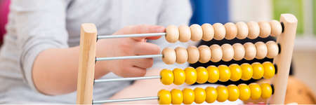 Foto de Close-up of young girl with studying problems counting on abacus - Imagen libre de derechos