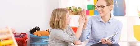 Foto de Young happy teacher congratulating good work to her little student - Imagen libre de derechos