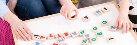 Foto de Close-up of young girl setting the word from wooden letters - Imagen libre de derechos