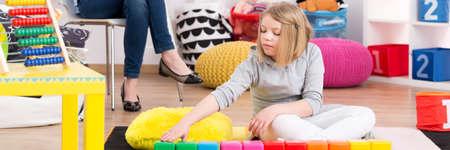 Foto de Young girl on psychotherapy playing with colorful blocks - Imagen libre de derechos