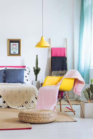 Photo pour Stylish bright bedroom with yellow lamp, armchair and skull poster - image libre de droit