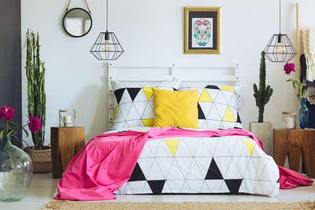 Photo pour Unique white bedroom with colorful pillows, geometric bedclothes and cactus - image libre de droit