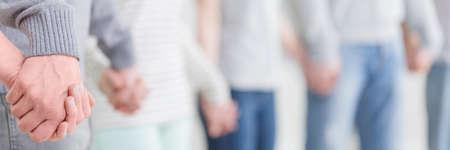 Foto de Group therapy patients standing and holding hands during session - Imagen libre de derechos