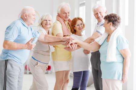 Photo pour Team of happy active seniors gathering hands together before the training - image libre de droit