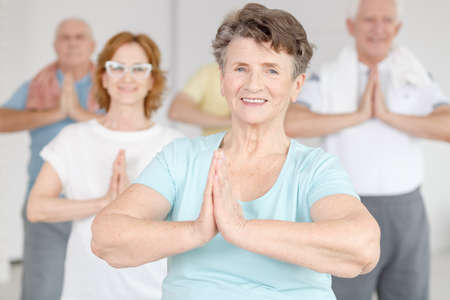 Photo pour Smiling active woman exercising at yoga classes together with her friends - image libre de droit
