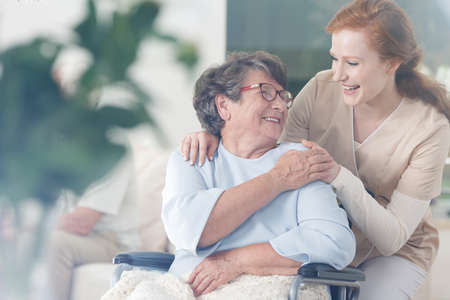Foto de Happy patient is holding caregiver for a hand while spending time together - Imagen libre de derechos