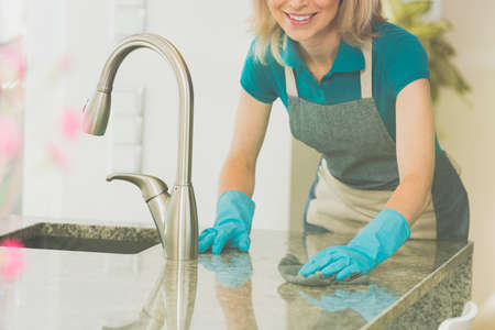 Photo for Woman wipes counter top and sink with glossy finish in modern kitchen - Royalty Free Image