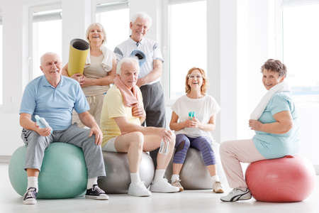 Photo for Older people smiling and posing for a photo at the gym - Royalty Free Image