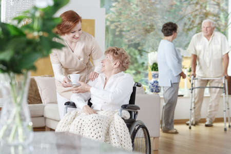 Foto de Friendly nurse gives a cup of tea to disabled woman on wheelchair in senior home - Imagen libre de derechos