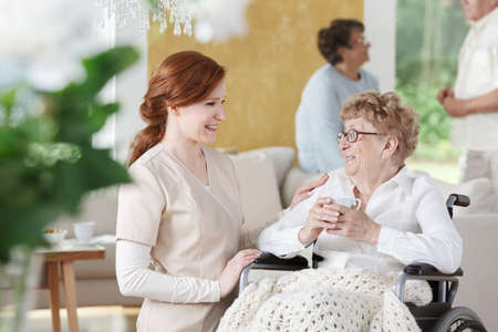 Foto de Older woman sits on wheelchair next to nurse and is holding a cup of coffee - Imagen libre de derechos