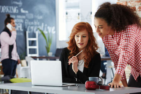 Foto de Young freelancers using the laptop in modern coworking office - Imagen libre de derechos