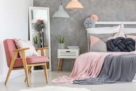 Photo pour Pink armchair with decorative cushion and big mirror in the bedroom corner - image libre de droit