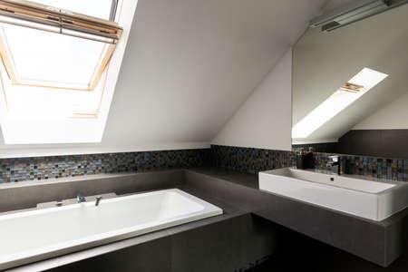 Foto de Light and spacious bathroom in the attic with windows - Imagen libre de derechos