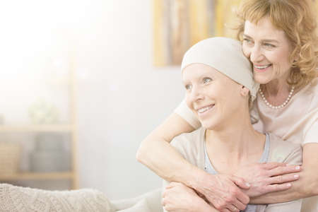 Photo pour Supportive older woman hugging her friend struggling with cancer - image libre de droit