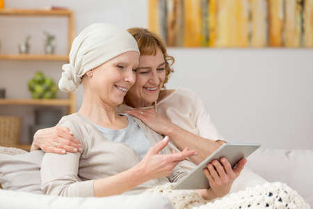 Photo pour Woman with cancer and her friend looking at photos on tablet - image libre de droit