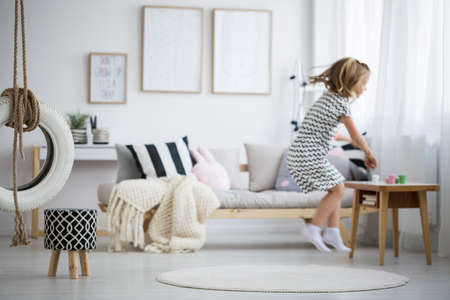 Photo pour Blonde girl in dress jumping in modern room with swing - image libre de droit