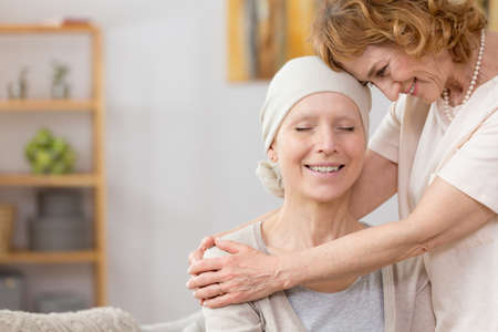 Photo pour Senior woman helping her friend suffering from cancer - image libre de droit