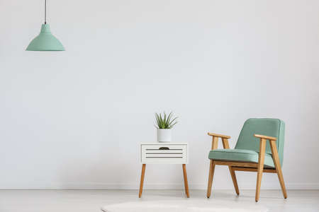 Photo for Photo of white wooden cupboard with fresh plant and mint lampshade - Royalty Free Image