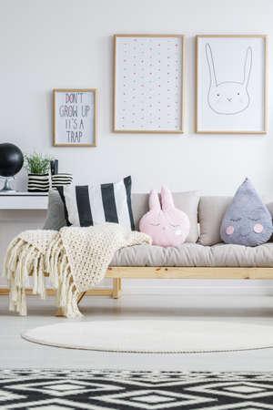Photo pour View of wooden nordic sofa in trendy children's room - image libre de droit