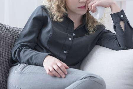 Foto de Pensive depressed woman sitting on a couch - Imagen libre de derechos