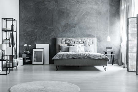 Photo for Modern bedroom with simple furniture, gray bedding and soft headboard - Royalty Free Image