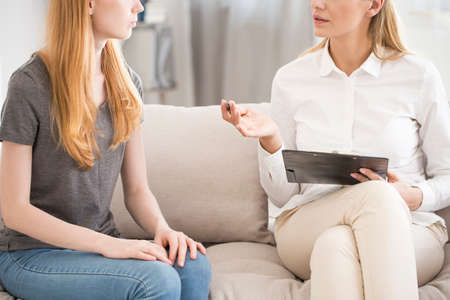 Foto de Consultation in a clinic, female psychiatrist writing down notes during therapy session for anxiety - Imagen libre de derechos