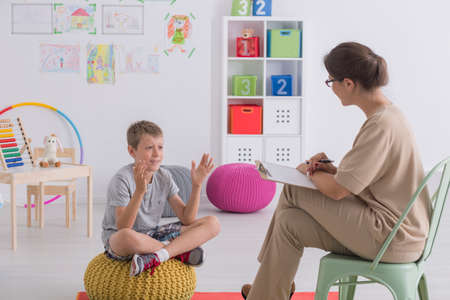 Foto de Child talking to therapist in colorful classroom with toys - Imagen libre de derechos