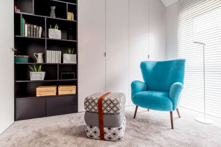 Photo pour Modern interior with cozy reading corner with black bookcase, blue armchair, pouf and big window with blinds - image libre de droit