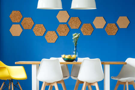 Foto de Royal blue wall in simple scandinavian dining room with wooden and white communal table, chairs and honeycomb cork wall decor - Imagen libre de derechos