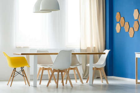Foto de Multifunctional scandinavian home interior with communal table, white and yellow chairs, blue wall, lamps and window with light curtains - Imagen libre de derechos