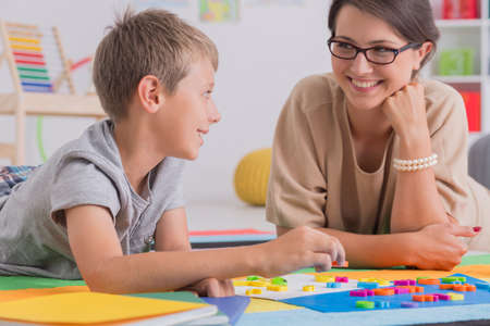 Foto de Blonde boy lying on floor with smiling elegant woman in colorful classroom - Imagen libre de derechos