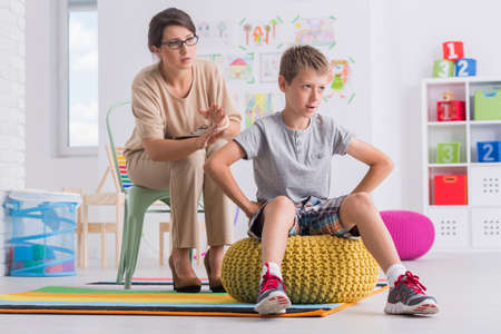 Foto de Offended child turning his back on female therapist in room with toys - Imagen libre de derechos