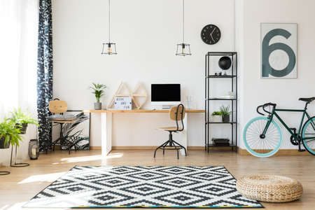 Photo pour Triangle shelves on a simple, wooden desk and floral poster hidden in the corner, behind a chair - image libre de droit