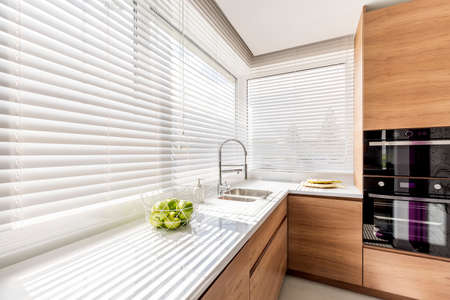 Foto de Modern bright kitchen interior with white horizontal window blinds, wooden cabinets with white countertop and household appliances - Imagen libre de derechos