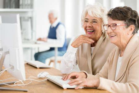 Photo pour Two elder women with glasses learning how to use computer together - image libre de droit