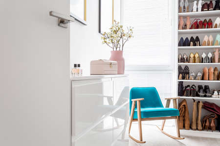 Photo pour White cabinets in elegant classic walk-in closet with open storage for shoes, door, blue vintage armchair and pastel decor - image libre de droit