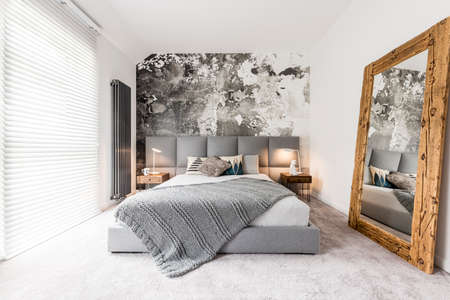 Photo pour King-size bed with gray square headboard, large rustic wooden mirror and textured wall in trendy minimalist apartment - image libre de droit