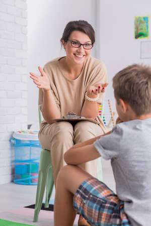 Foto de Smiling young woman wearing glasses talking to boy in white room - Imagen libre de derechos